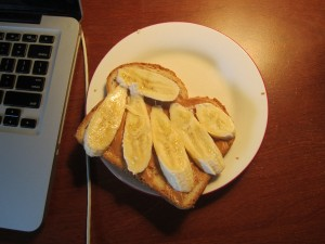 Peanut butter and banana sandwich next to a laptop