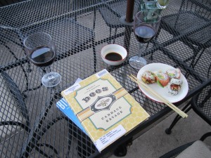 two books next to a plate of sushi and two glasses of wine